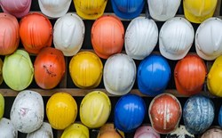 collection of colorful hard hats hang in rows