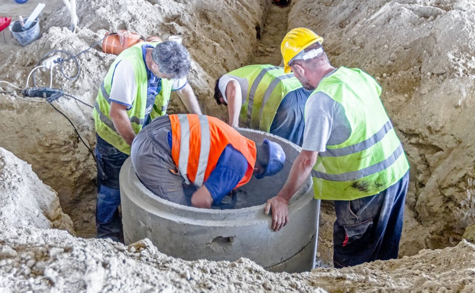 construction workers in pit utility tunneling method