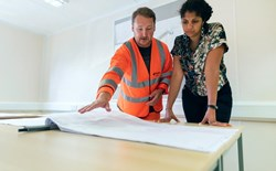 man and woman looking at engineering blueprint in white room