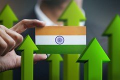 India flag held in hand and green arrows pointing upward