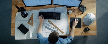 man working on computer at desk with blueprints hard hat and engineering tools