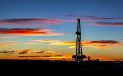 silhouette of an oil rig at sunset with clouds and vivid colors