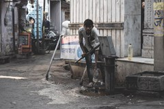 man in New Delhi India fills a water bottle from a pump on the street