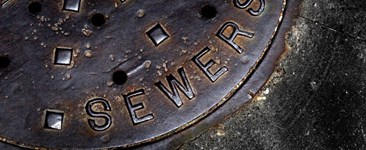 Iron manhole cover with the word sewers on it