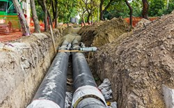 two large black pipes in open trench surrounded by trees and orange fence