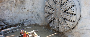 tunnel boring machine coming through rock surface with workers nearby